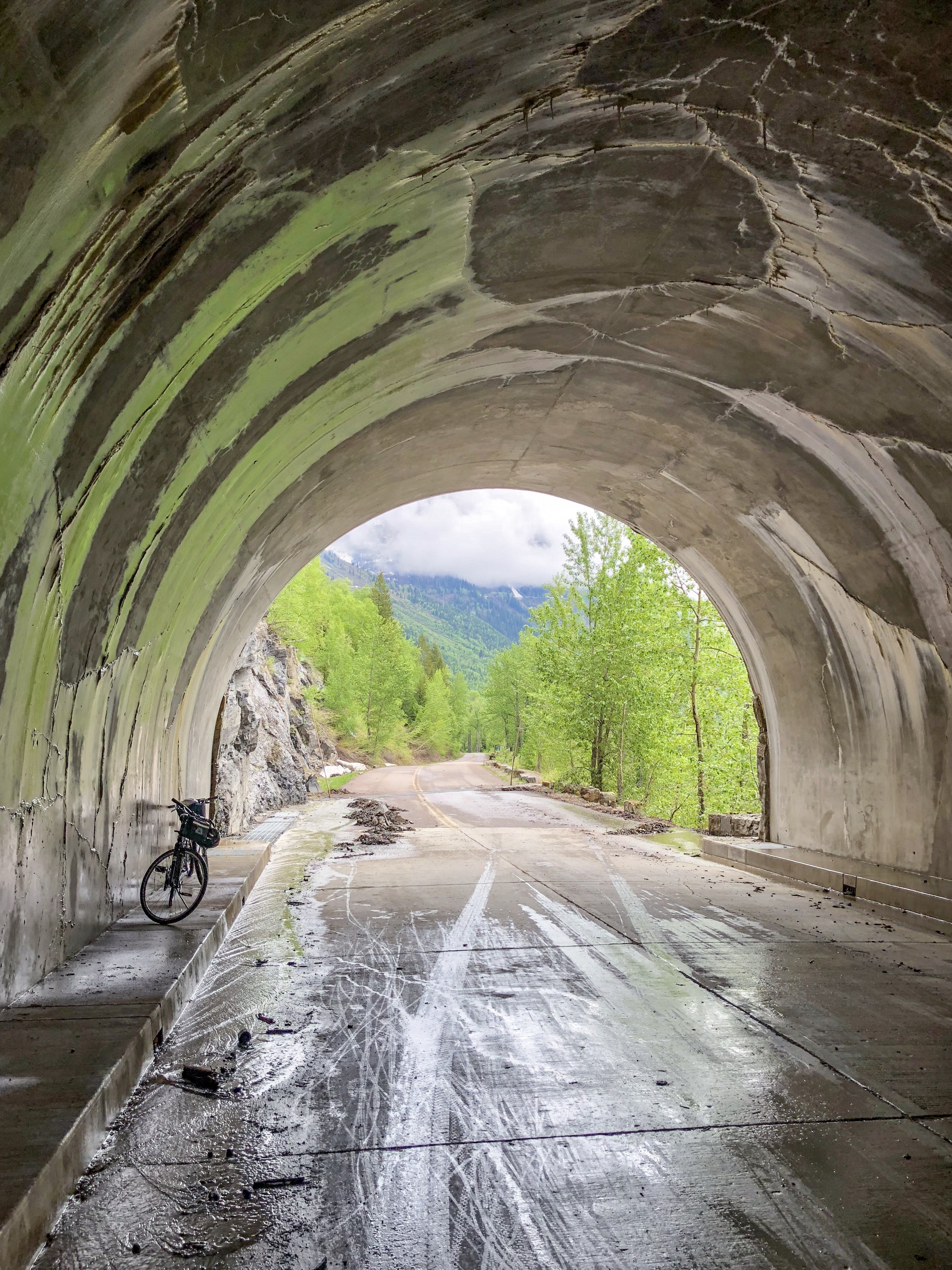 View of Going to the Sun Road in Glacier National Park from a tunnel with a bicycle